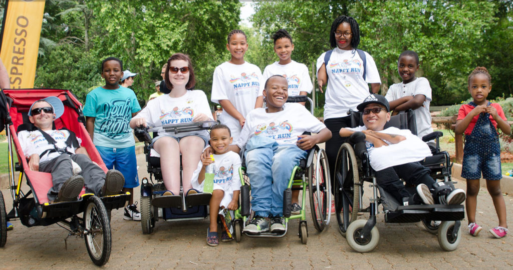 A group of 11 people, 4 in their wheelchair's, grouped together in preparation for the start of The Nappy Run